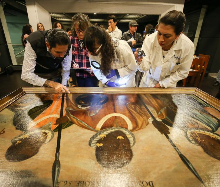 Expertos del Museo Nacional (MuNa) de Ecuador revisan la obra 'Los tres mulatos de Esmeraldas'.