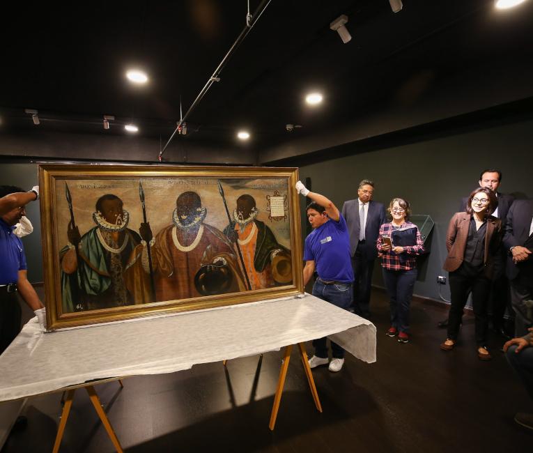 Operarios apoyan en una mesa la obra virreinal de 1599 'Los tres mulatos de Esmeraldas'