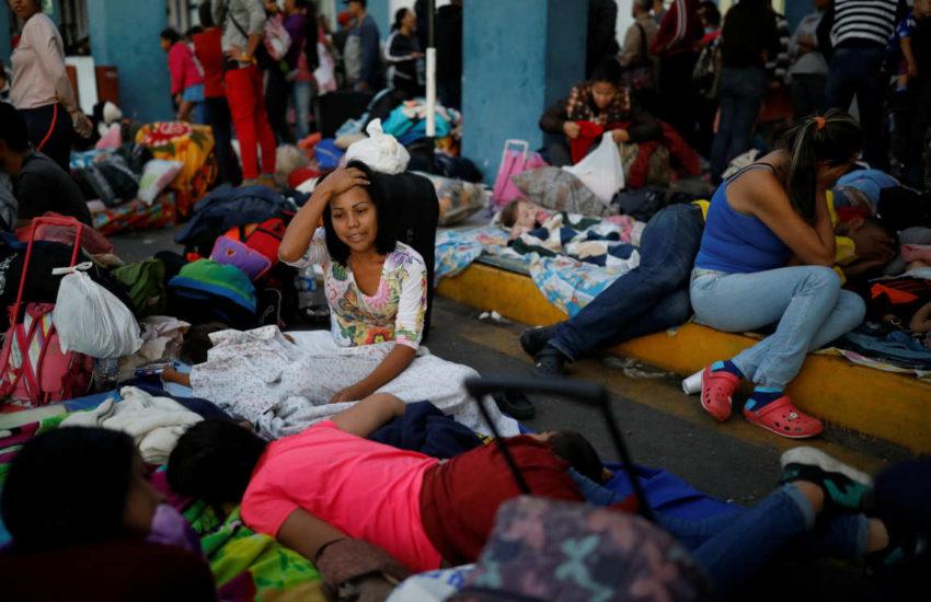 Ciudadanos venezolanos descansan en el paso fronterizo entre Ecuador y Perú.