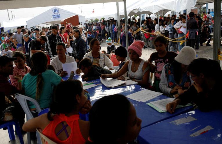 Ciudadanos venezolanos realizan trámites en el paso fronterizo de Tumbes, en la frontera de Ecuador y Perú.