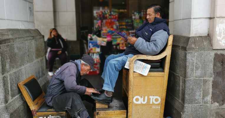 Luis Gálvez limpia los zapatos de uno de sus clientes.