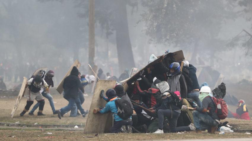 Manifestantes se resguardan atrás de escudos de madera durante las protestas del domingo 13 de octubre de 2019.