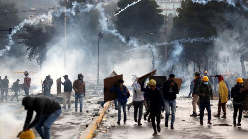 Manifestantes corren entre los gases lacrimógenos lanzados por la policía en una nueva jornada de choques el domingo 13 de octubre de 2019, en Quito.