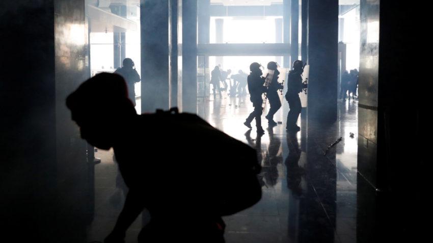 Militares y manifestantes corren en el interior de la Asamblea Nacional.