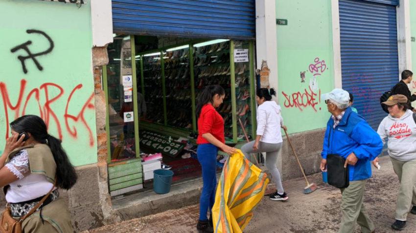 Ciudadanos limpian los exteriores de un negocio afectado por las protestas en el Centro Histórico de Quito.
