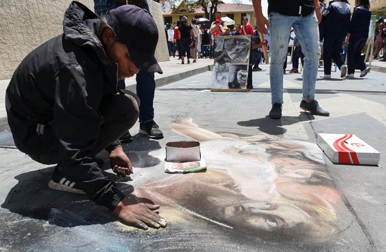 Un artista callejero pinta en una de las calles de Loja.