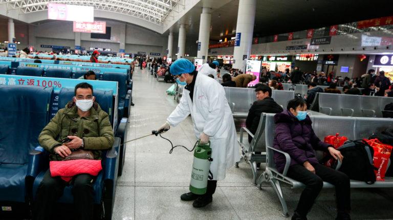 Un operario desinfecta una zona de espera para pasajeros en la estación de tren de Nanchang, China.