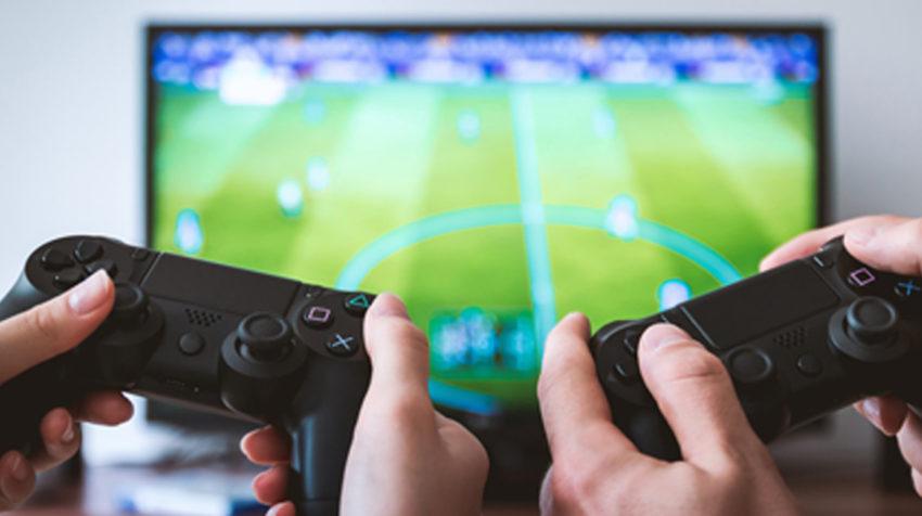 Imagen de dos personas jugando FIFA 21 en PlayStation.