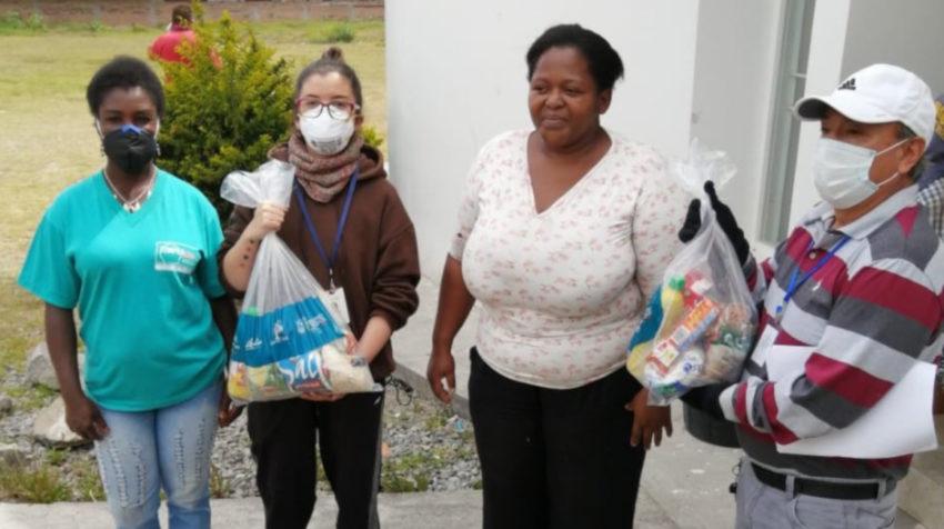 Personas reciben los kits de alimentos en Imbabura el viernes 20 de marzo de 2020.