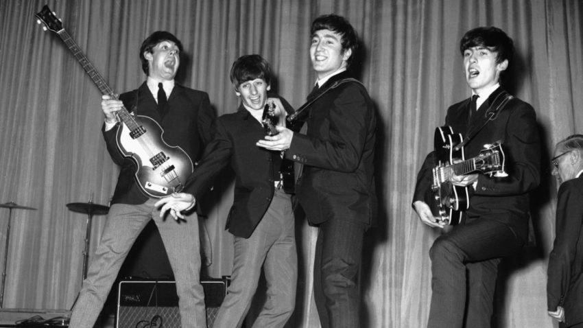 The Beatles en un escenario, en 1963, año en el que lanzaron su primer disco.