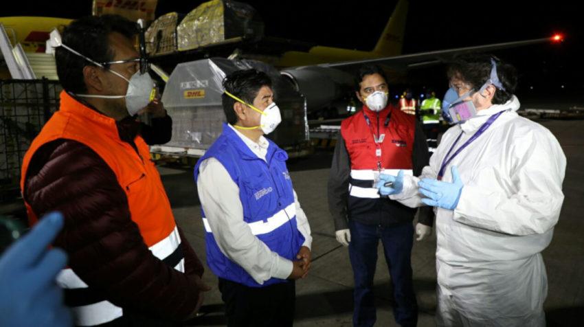 El alcalde de Quito, Jorge Yunda (azul) en el aeropuerto Mariscal Sucre de la capital, el 20 de abril de 2020, durante la llegada de 5.000 pruebas PCR.