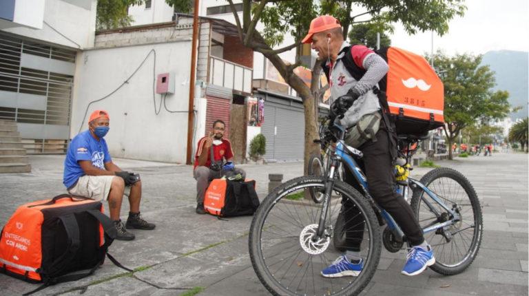 Un grupo de repartidores, entre ellos venezolanos, espera sus pedidos para distribuir en Quito, el 30 de marzo de 2020.