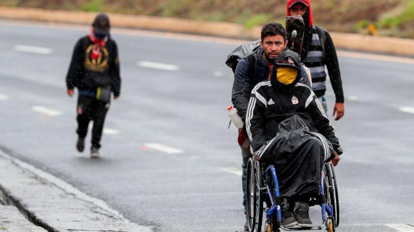 Ciudadanos venezolanos, uno de ellos con discapacidad, transitaban el jueves 28 de mayo en una carretera cercana a Quito (Ecuador).