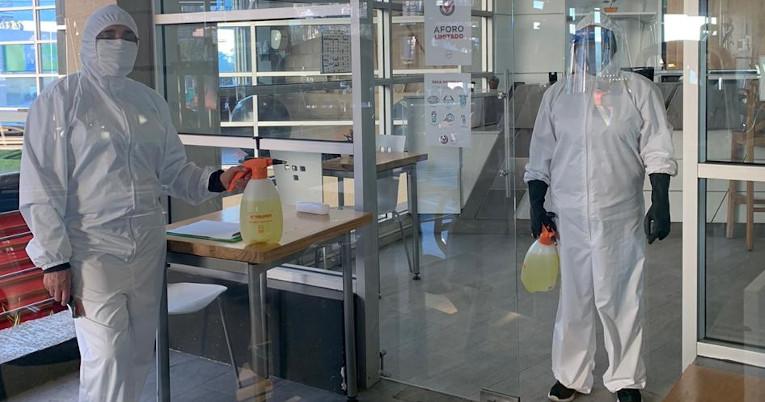 Personal de limpieza en la entrada de un gimnasio en Quito.
