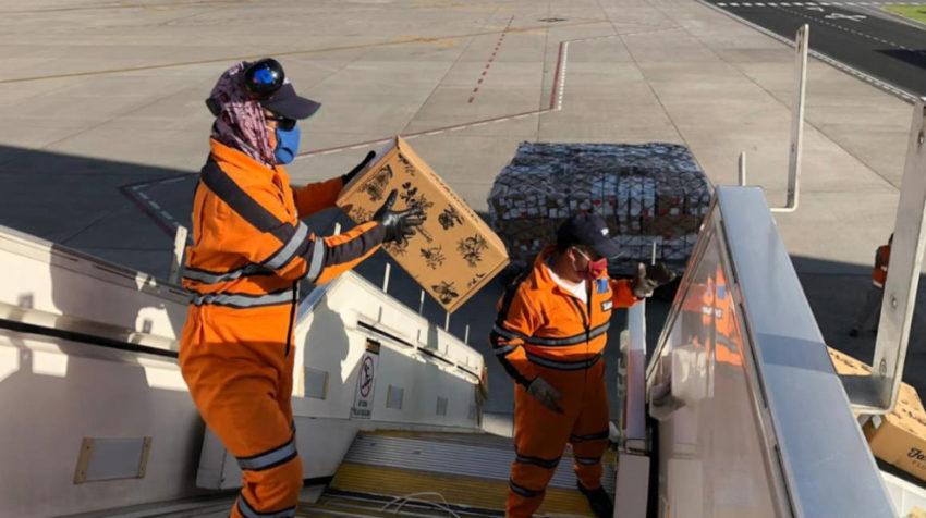 Personas en el Aeropuerto de Quito cargan un avión de pasajeros con flores, el 29 de abril.