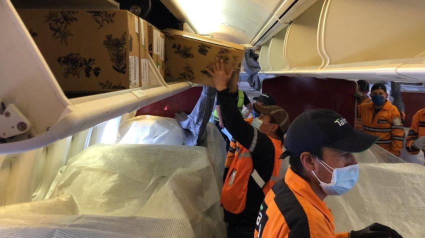 Trabajadores de Latam acomodan las flores en la cabina de pasajeros, el 29 de abril, en Quito.