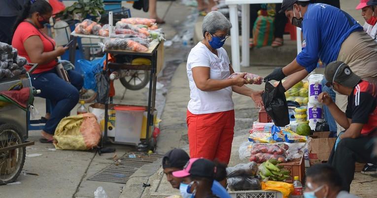 Una mujer compra a un vendedor ambulante en la Casuarina, en la Av. Perimetral, de Guayaquil, el 24 de mayo.