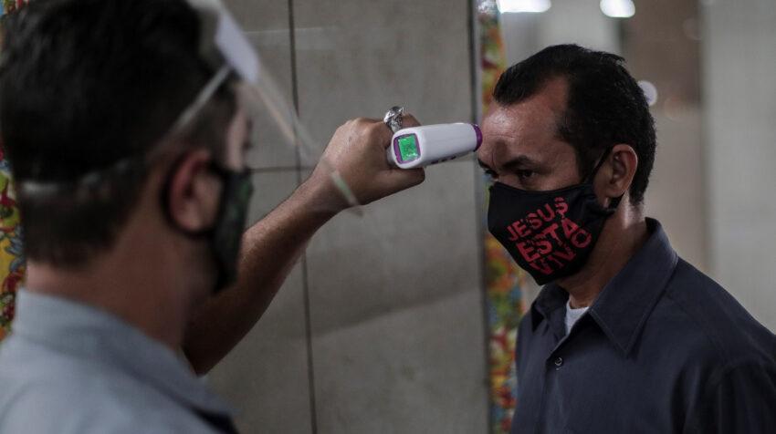 Un guardia mide la temperatura a un hombre que entra a un mercado en Brasil, el 24 de junio.