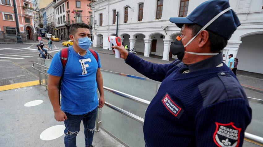 Un guardia de seguridad le toma la temperatura a un ciudadano en Quito antes de subirse a un bus de transporte público, el 10 de junio.