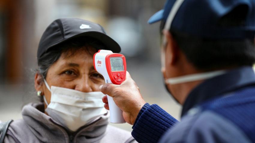 Una mujer con una máscara mientras el personal de seguridad le toma la temperatura antes de abordar un transporte público, este miércoles 10 de junio de 2020 en una calle de Quito, Ecuador.