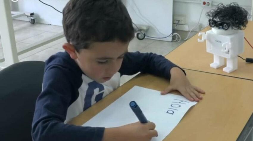 Niño escribiendo junto a Nacho.