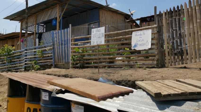 Un letrero en Cañaveral destaca la importancia de lavarse las manos junto a otro que anuncia la venta de botellones de agua.