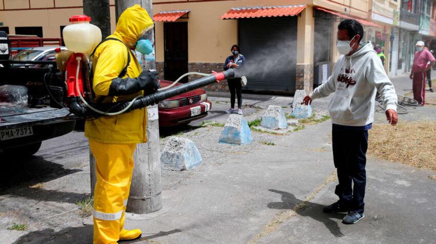 Personal sanitario de Quito desinfecta a un hombre, el 20 de agosto de 2020.