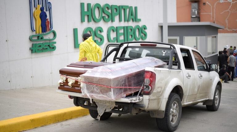 Empleados de una funeraria recogen al ataúd con un fallecido por Covid-19, en el hospital Ceibos del IESS, el 1 de abril de 2020.