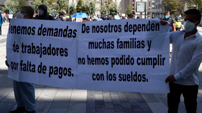 Proveedores del Estado sostienen cartelas durante una protesta en Quito, el 7 de agosto de 2020.