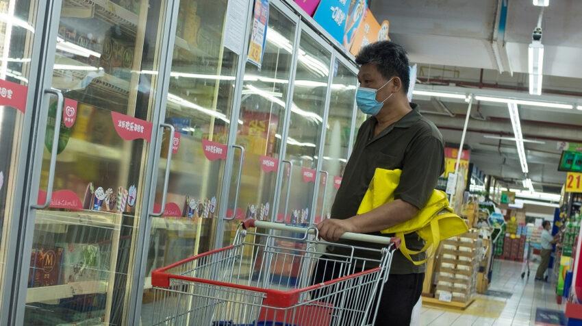 Foto referencial. Un hombre en Beijing mira a productos congelados en un supermercado de la capital China, el 13 de agosto de 2020.