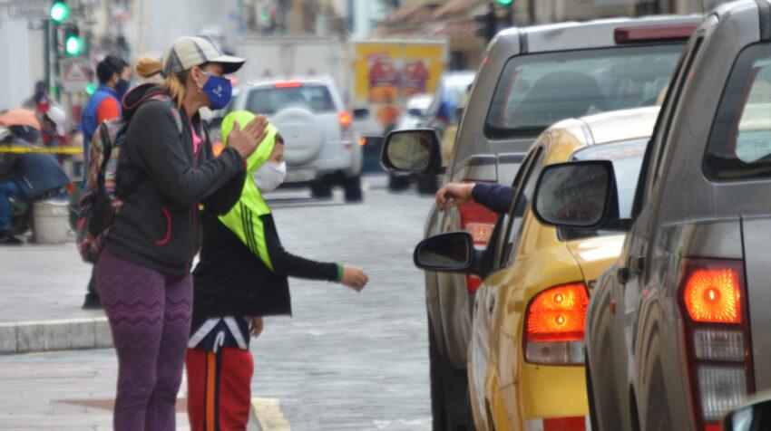 Una mujer y un menor de edad piden una ayuda económica en Cuenca, el 26 de junio de 2020.