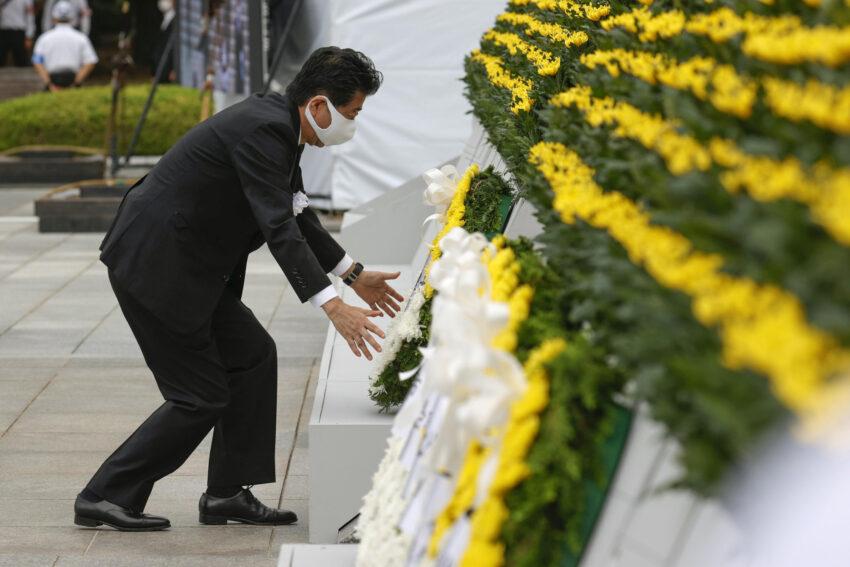 El primer ministro de Japón, Shinzo Abe, con una máscara protectora, ofrece una corona de flores para las víctimas del bombardeo atómico de 1945, en el Parque Memorial de la Paz en Hiroshima, Japón, el 6 de agosto de 2020, en el 75 aniversario del bombardeo atómico de la ciudad.