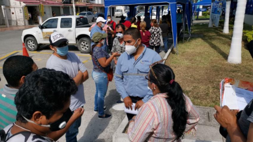 Ciudadanos en los exteriores de CNEL mientras escuchan las explicaciones de un funcionario este 3 de agosto de 2020.