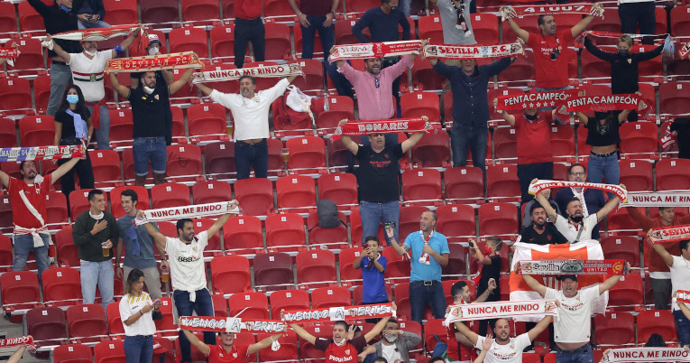 Hinchas de Sevilla con banderas y bufandas alientan a su equipo en la final de la Supercopa de Europa.