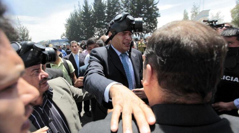 El expresidente Rafael Correa es protegido del gas lacrimógeno, el jueves 30 de septiembre de 2010, durante una protesta de efectivos policiales.