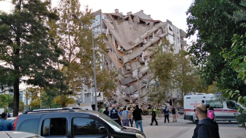Lugareños observan un edificio dañado después de un fuerte terremoto, 30 de octubre de 2020.
