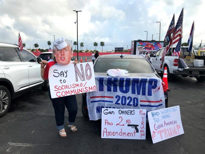 Unas personas sostienen carteles a favor del presidente Donald Trump mientras participan una manifestación multitudinaria contra el comunismo el 10 de octubre de 2020, en Miami, Florida (EEUU).