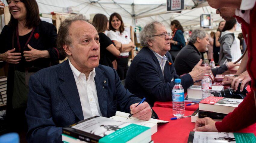El escritor Javier Marias (i) firma ejemplares de su libro a sus lectores junto a Ian Gibson (c) y Manuel Rivas (d) durante la diada de Sant Jordi, la tradicional fiesta del libro y de la rosa, en abril de 2018.