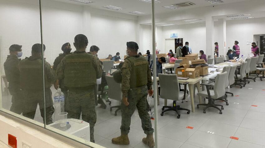 Militares custodian las actas mientras los digitalizadores trabajan en la Junta Electoral del Guayas.