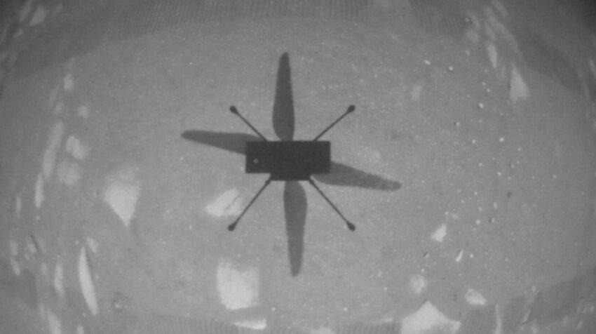 El Ingenuity captado por una cámara a bordo apuntando hacia abajo mientras el helicóptero estaba en el aire.
