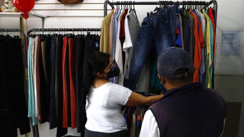 Una vendedora de Amigui le muestra ropa a un cliente, en Quito, el 1 de abril de 2021.