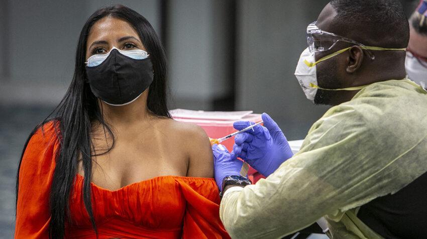 Sigrey Gonzalez Flores recibe una dosis de la vacuna de Pfizer en el Aeropuerto de Miami.
