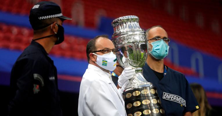Trabajadores sanitarios cargan la Copa América previo al partido inaugural entre Brasil y Venezuela.