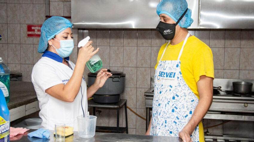 Una trabajadora de las Brigadas de Limpieza de La Fabril brinda asesoría a un cliente en Ecuador, en 2020.