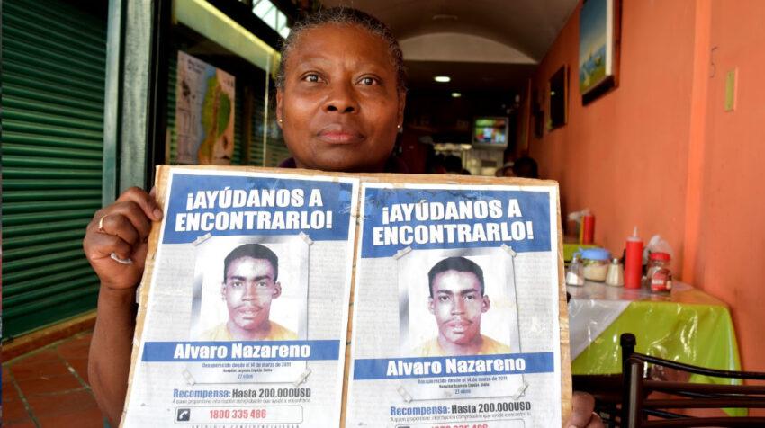 Maribel Ángulo muestra un cártel con dos volantes sobre la desaparición de su hijo, Álvaro Nazareno.