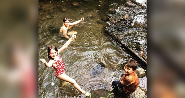 Los niños bañándose en el río con el jabón de manzanilla.