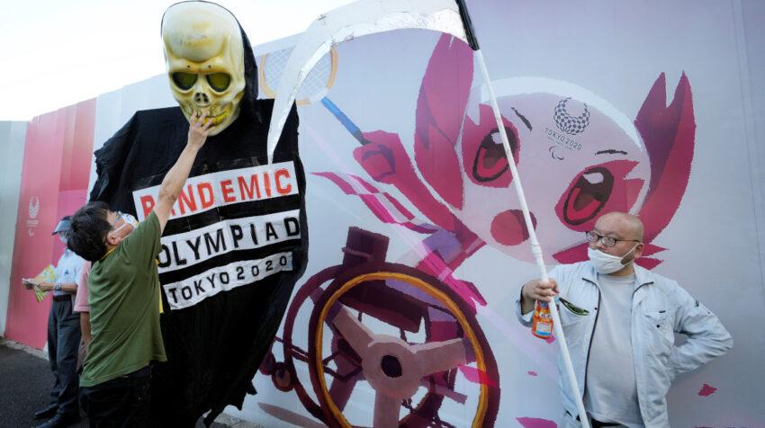 Dos personas participan de una protesta en contra de los Juegos Olímpicos, en Tokio, el 16 de julio de 2021.