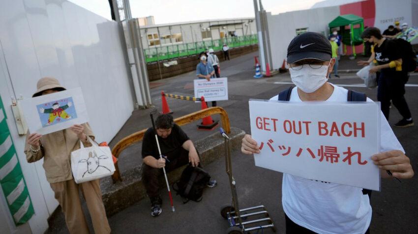 Personas muestran carteles en contra de Thomas Bach, presidente del COI, en Tokio, el 16 de julio de 2021.