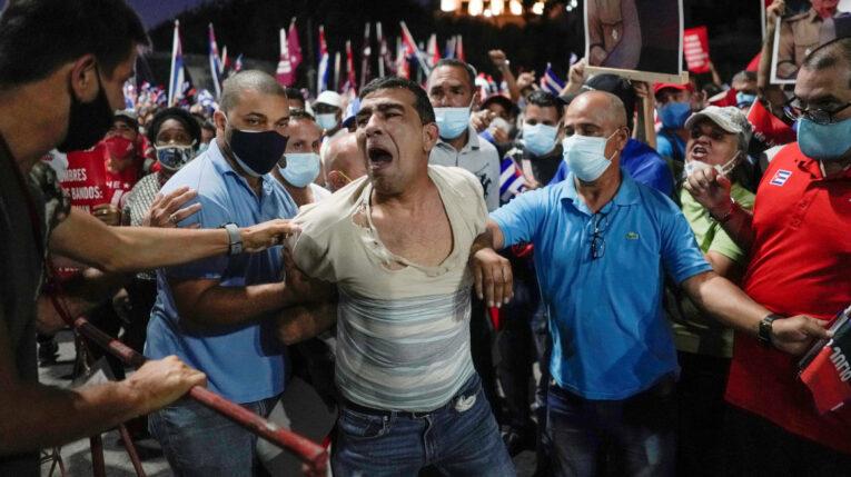 Personas detienen a un contramanifestante durante una concentración a favor del gobierno en La Habana, Cuba. 17 de julio de 2021.