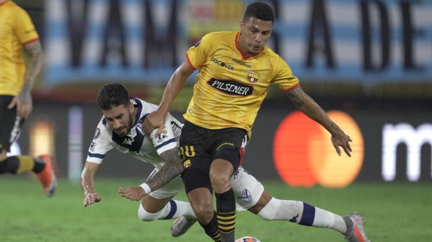 Luis Fernando León (d) de Barcelona SC disputan un balón con Juan Martín Lucero (i) de Vélez en un partido por Copa Libertadores, el 21 de julio de 2021.